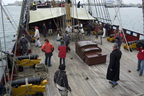 Le second capitaine vétu d'une grande vareuse noire transmet des ordres à ses équipiers.
